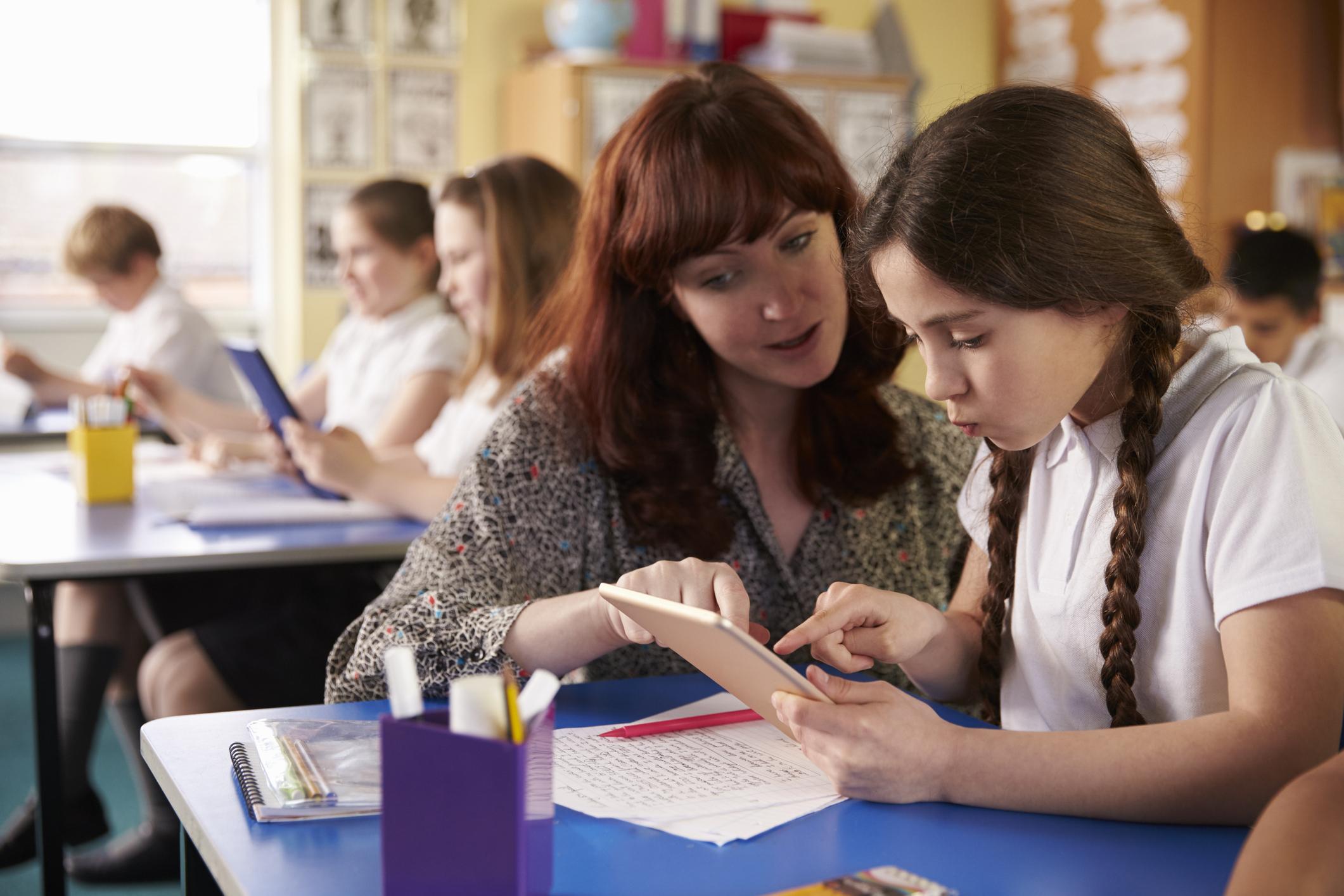 Teacher helping school girl -fulfilling career